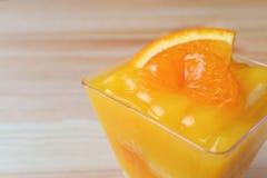 Cerrado encima de una torta vibrante de la mandarina del color remató con la naranja fresca en bol de vidrio en la tabla de mader Imagenes de archivo