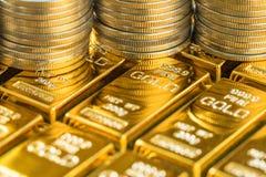 Cerrado encima del tiro de las barras de oro brillantes con la pila de monedas como negocio Foto de archivo libre de regalías
