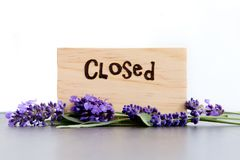 Cerrado - palabra quemada en madera con las flores púrpuras de la lavanda en pizarra con el fondo blanco foto de archivo