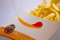 Cerrado para arriba de las patatas fritas de Burger King en el fondo blanco Foco en el logotipo de Burger King imagenes de archivo