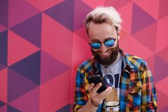Cerrado para arriba de un hombre joven del inconformista feliz lea un mensaje en su tel?fono celular, en un fondo colorido fotos de archivo libres de regalías
