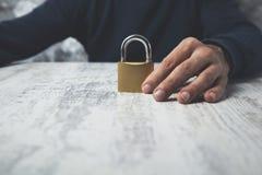 Cerradura de la mano del hombre en la tabla foto de archivo