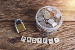 Cerradura de la seguridad del oro con la contraseña y las monedas llenas con el tarro, palabras Imágenes de archivo libres de regalías