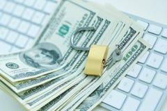 Cerradura de la seguridad en billetes de dólar con el teclado de ordenador blanco Foto de archivo libre de regalías