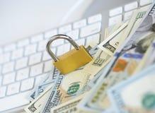 Cerradura de la seguridad en billetes de dólar con el teclado de ordenador blanco Fotos de archivo libres de regalías