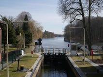 Cerradura del barco que lleva en un canal lateral de un río Imagen de archivo libre de regalías
