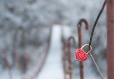 Cerradura roja bajo la forma de corazón en puente colgante a través del th Foto de archivo