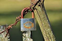 Cerradura vieja en el alambre de púas Foto de archivo