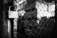 Cerradura vieja en la cerca de alambre oxidada Foto de archivo