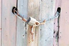 Cerradura y cadena en viejo fondo de madera de la textura Fotos de archivo