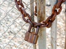 Cerradura y cadena resistentes oxidadas viejas de cojín en una cerca fotos de archivo libres de regalías