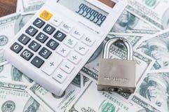 Cerradura y calculadora en fondo del billete de dólar Imagenes de archivo