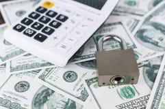 Cerradura y calculadora en fondo del billete de dólar Fotografía de archivo