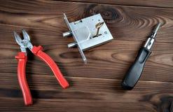 Cerradura y herramientas de puerta en una superficie de madera Foto de archivo libre de regalías