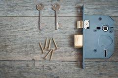 Cerradura y llaves de puerta vistas contra un fondo de madera con el espacio de la copia Foto de archivo libre de regalías