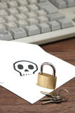 Cerradura y llaves delante del sobre con el cráneo escrito en el teclado de ordenador de reclinación de la tarjeta Foto de archivo libre de regalías