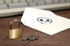 Cerradura y llaves delante del sobre con el cráneo escrito en el teclado de ordenador de reclinación de la tarjeta Imagen de archivo libre de regalías