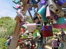 Cerraduras coloridas que cuelgan de una reproducción de la torre Eiffel imagenes de archivo
