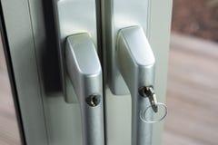 Cerraduras en las puertas de cristal al jardín como defensa para el robo Fotografía de archivo libre de regalías
