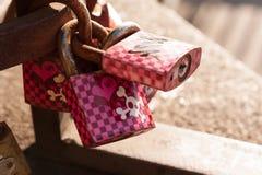 Cerraduras rosadas del amor con los cráneos y la bandera pirata Fotografía de archivo