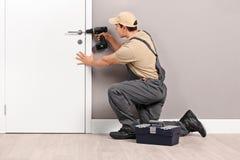 Cerrajero joven que instala una cerradura en una puerta Imagenes de archivo