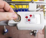Cerrando y desbloqueando la carretilla del supermercado con una moneda euro Imágenes de archivo libres de regalías
