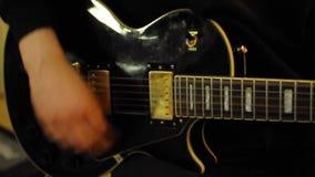 Cerrar la mano del hombre tocando la guitarra eléctrica. Fingeres masculinos del guitarrista que rasguean las secuencias almacen de video