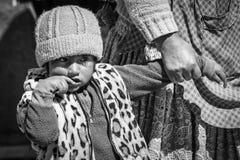 CERRILLOS - BOLIVIA, AUGUST 10, 2017: Unidentified child in Cerrillos village on Bolivian Altiplano. Near Eduardo Avaroa Andean Fauna National Reserve with blue Stock Photo