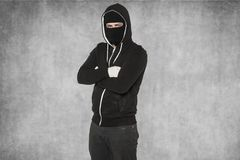 Certain attitude of a masked suspect. Wearing black cloths Royalty Free Stock Photo