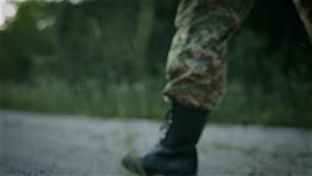 Certain military man walk on the sandy road. In camouflage stock video