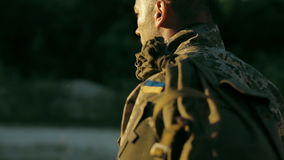 Certain military man walking across sandy road stock footage