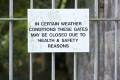 Certain weather conditions these gates will shut sign at park entrance. Uk royalty free stock images
