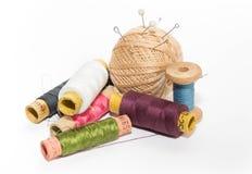 Certe delle bobine e di una palla colorate multi dei fili di beige con i perni Immagine Stock Libera da Diritti