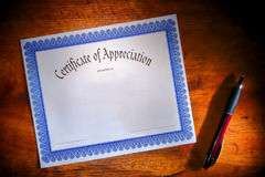 Certificate of Appreciation Blank Document on Desk. Certificate of appreciation reward blank paper document ready to fill out with text and ballpoint ink pen for Stock Photo