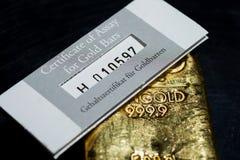 The certificate of assay for gold bars lies on a cast gold ingot. Gehaltszertifikat für Goldbarren is certificate of assay for gold bars royalty free stock photos
