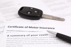 Certificate of motor insurance. With car key and pen Royalty Free Stock Photo