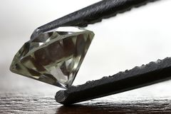 Diamond. Certified 0.45 ct brilliant cut diamond with laser inscription held by tweezers stock photo