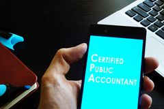 Certified public accountant CPA. Hand holding phone with sign Certified public accountant CPA Stock Photos