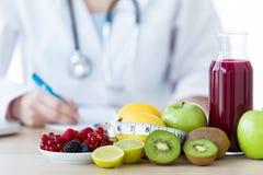 Certos frutos tais como maçãs, quivis, limões e bagas na tabela do nutricionista fotografia de stock royalty free