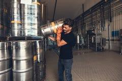 Cervecero con el barrilete en el almacén de la fábrica de la cervecería imagen de archivo