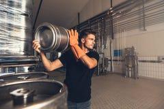 Cervecero con el envase grande del metal en la cervecería imagen de archivo libre de regalías