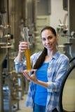 Cervecero de sexo femenino que sostiene el cilindro del aerómetro Foto de archivo libre de regalías