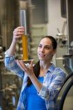 Cervecero de sexo femenino que sostiene el cilindro del aerómetro Imagenes de archivo