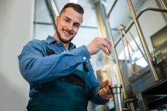 Cervecero que comprueba la cerveza con el aerómetro Imagen de archivo libre de regalías