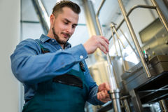 Cervecero que comprueba la cerveza con el aerómetro Foto de archivo