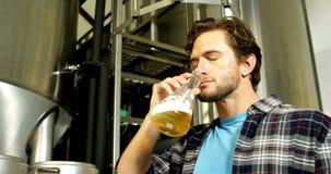 Cervecero que comprueba la pinta de la cerveza 4k almacen de metraje de vídeo