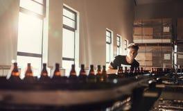 Cervecero que mira el transportador con las botellas de cerveza fotografía de archivo libre de regalías