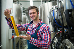 Cervecero que sostiene el cilindro del aerómetro Fotos de archivo