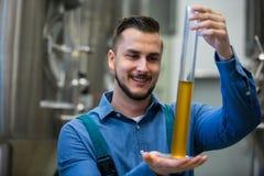 Cervecero que sostiene el cilindro del aerómetro Foto de archivo libre de regalías