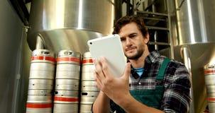 Cervecero que usa la tableta digital en la fábrica 4k de la cervecería almacen de video